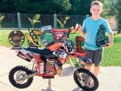 Victor, com a moto e troféus conquistados durante o campeonato